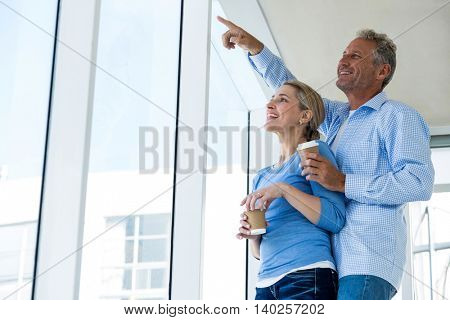 Smiling man pointing while standing by woman at home