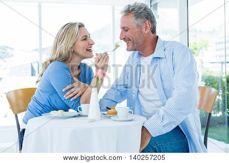 Happy mature woman feeding man while sitting at restaurant