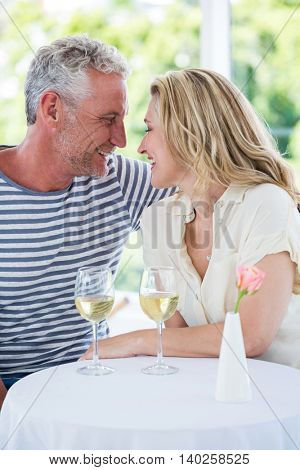 Romantic smiling mature couple with white wine while sitting at restaurant