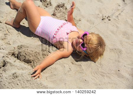 cute happy little girl play on sand beach