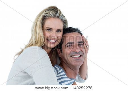 Portrait of smiling man carrying woman piggyback against white background