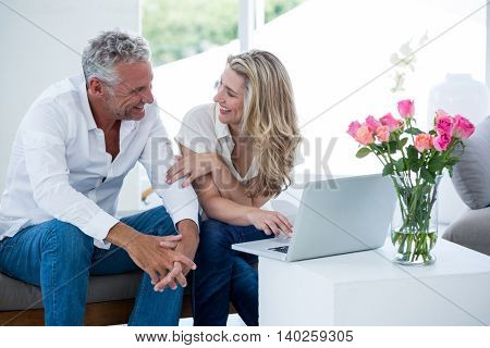 Smiling mature couple with laptop while sitting at home