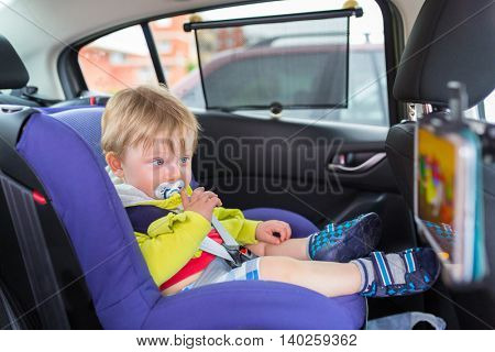 Baby boy in a car on child safety seat watching cartoon on the tablet