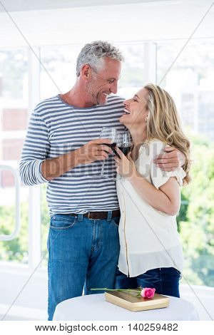 Romantic smiling mature couple with red wine while sitting at restaurant