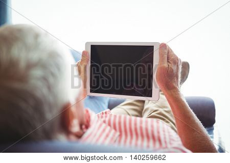 Lying on a couch senior man looking at digital tablet on a sunny day