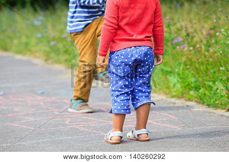 kids playing hopscotch on playground outdoors in summer