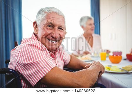 Senior man smiling at the camera during the lunch