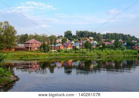 View of quiet provincial town of Ples on shore of pond in summer twilight Russia