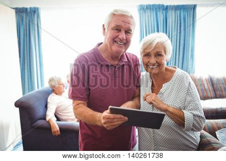 Smiling senior people looking at the camera holding a digital tablet