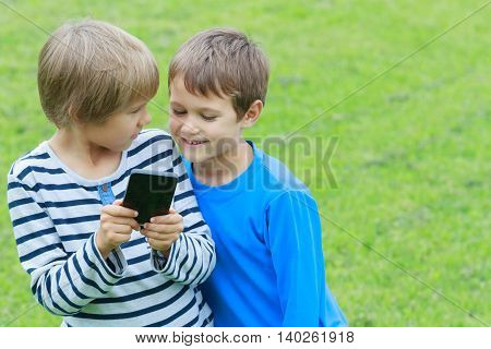 Children with mobile phone. Boys smiling, looking to phone, playing games or using application. Outdoor. Technology education leisure friendship people concept