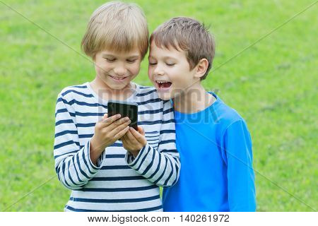 Two boys with mobile phone. Children smiling, looking to phone, playing games or using application. Outdoor. Technology education leisure people concept