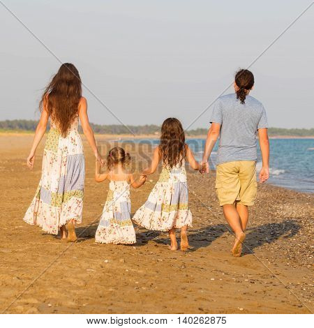 Happy family having fun together at sunset on the beach