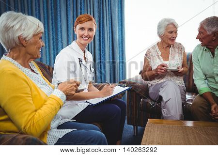 Smiling nurse looking at camera in the middle of senior persons