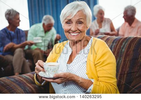 Smiling senior woman holding a cup of coffee looking at camera