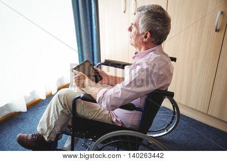 Senior man using a digital tablet in the wheelchair
