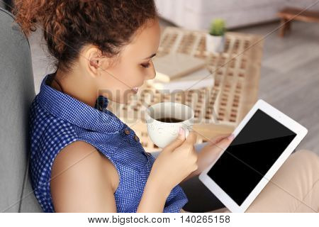 Beautiful African American girl with coffee and tablet on armchair