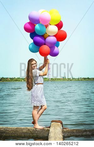 Happy woman with colorful balloons on river coast