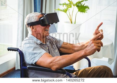 Senior man in a wheelchair using a virtual reality device in a retirement home