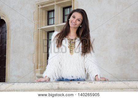 Attractive Young Woman Posing On A Background Of A Concrete Wall
