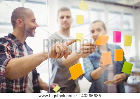 Business people sticking adhesive notes on glass window in creative office