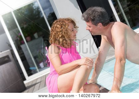 Honeymoon: Happy Young Newlyweds Smiling And Relaxing Near Hotel Pool. Horizontal Shape, Rear View,