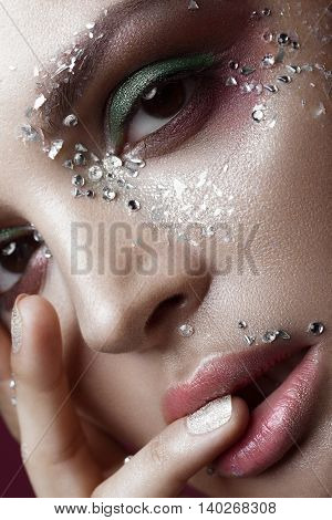 Beautiful girl with a bright color make-up and crystals on the face. Close-up portrait. Beauty face. Picture taken in the studio.