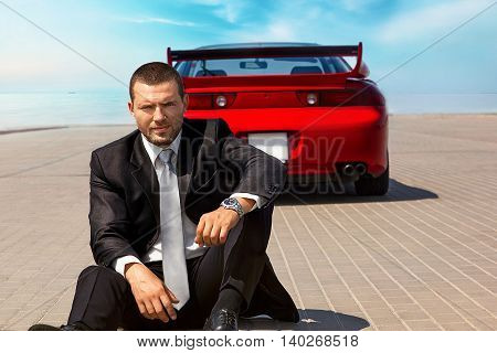 handsome young businessman near his red car