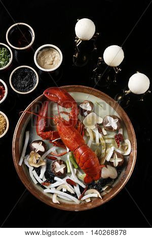 Red steamed lobster with mushroom in plate on black background
