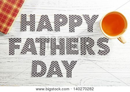 Happy Father's Day concept. Cup of tea and gift box on wooden background