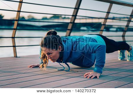Woman doing push-ups by the river, toned image, horizontal image