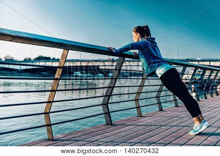 Woman exercising by the river, toned image, horizontal image
