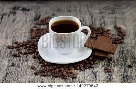 Aromatic Invigorating Cup Of Black Coffee Powder, Chocolate And  Beans Scattered On The Table