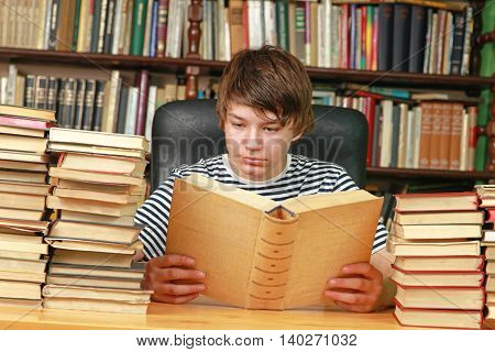 Teenage Boy Reading Book in School Library