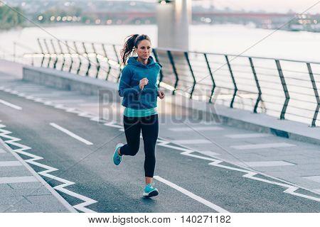 Woman running on riverside, toned image, horizontal image