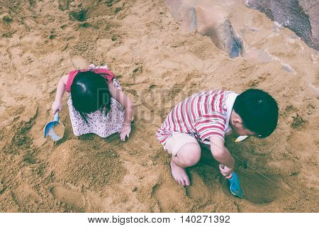 Top view. Happy brother and sister playing with sand. Adorable asian children have fun digging in the sand on a summer day. Vintage tone. Outdoors.
