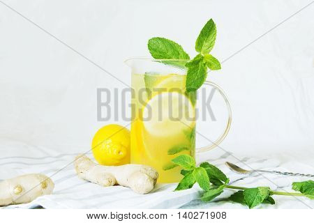 Lemonade with ginger and mint in kitchen. Home made ginger lemonade on striped napkin or towel. Healthy drink lemonade.