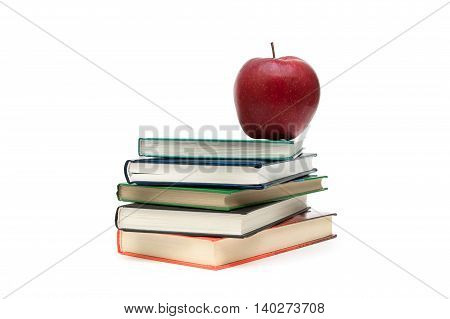 stack of books and red apple on a white background. horizontal photo.