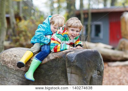 Two little kid boys in colorful rain jackets and gumboots having fun with playing on forest playground on warm, autumn day, outdoors. Siblings hugging and laughing together.