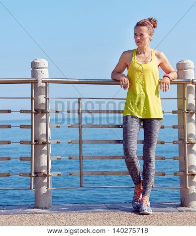 Woman In Fitness Outfit Looking Into Distance At Embankment