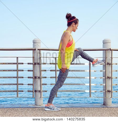 Young Healthy Woman In Fitness Outfit Stretching At Embankment