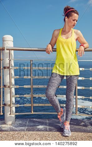 Healthy Woman In Fitness Outfit Looking Aside At Embankment