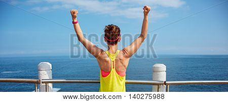 Young Healthy Woman In Fitness Outfit Rejoicing At Embankment