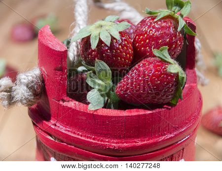 Red wooden basket full of delicious strawberries