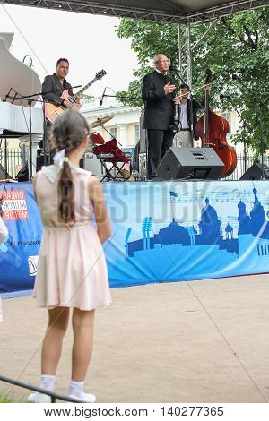 St. Petersburg, Russia - 23 July, Girl near the stage with the musicians, 23 July, 2016. Speech by David Goloschekin with his jazz group on the Arts Square in St. Petersburg.