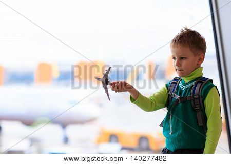 little boy playing with toy plane in the airport, kids travel