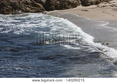 This is an image of the incoming tide taken in morning sunlight at Point Lobos State Preserve in California, U.S.A.
