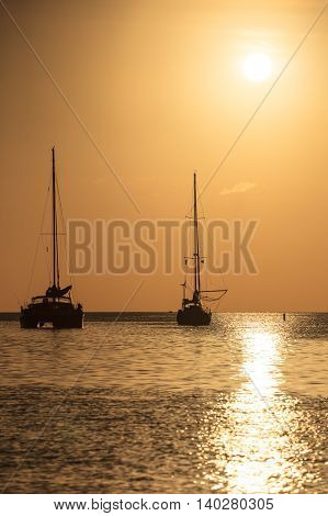 Sailboat silhouette at sunset in a Caribbean ocean with a burnt orange sky. Sailboat and catamaran backlit at dusk. White sun reflects on the ocean in Saint Lucia.