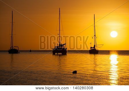 Sailboats backlit in Caribbean ocean with vivid yellow orange sunset. Boats and catamarans in silhouette at dusk. Beautiful gold sky with white sun reflect on the ocean in Saint Lucia.