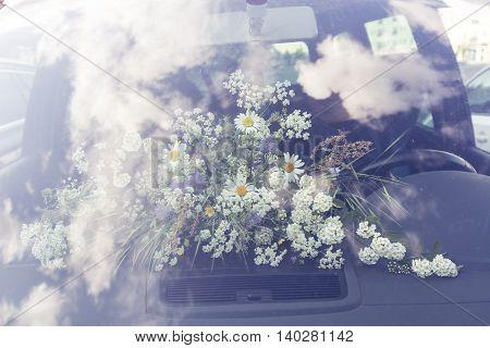 bouquet of field flower behind a windshield in a car