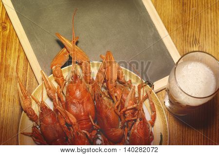 Boiled crawfish, glass of light beer and black chalkboard on a wooden table. Top view, vintage filtered picture.